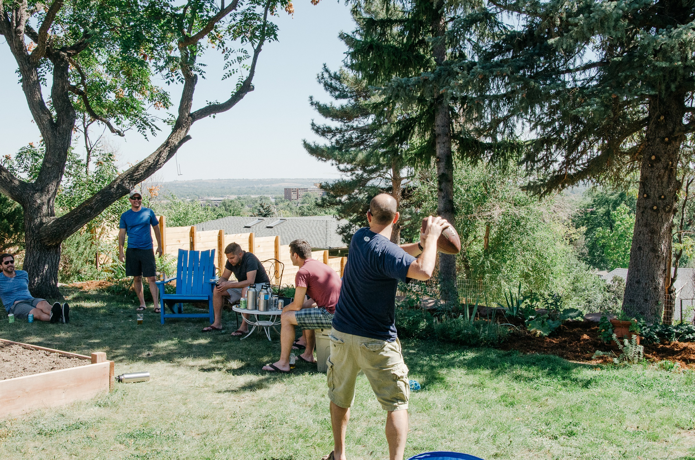 Brian and the groomsmen throw the football around before his wedding in Boulder, Colorado. Wedding photography by Max Salzburg of Sonja K Photography.