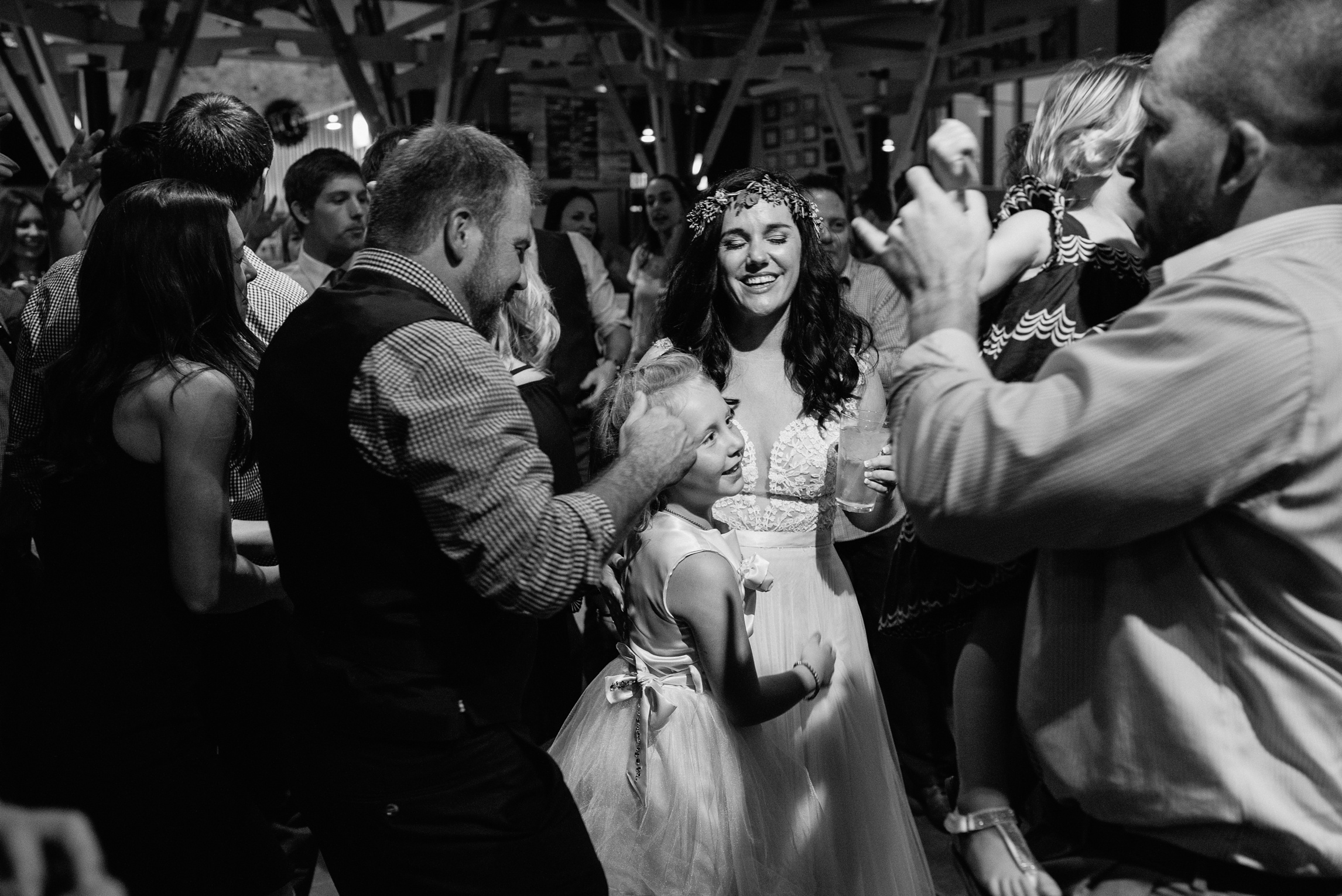 A bride and groom dance with their daughter on their wedding day. Wedding photography by Sonja Salzburg of Sonja K Photography.