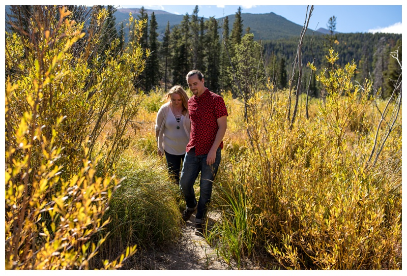 Stephanie and Daniel walk on the trail near Sprague Lake in Rocky Mountain National Park in Colorado. Engagement photography by Sonja Salzburg of Sonja K Photography.