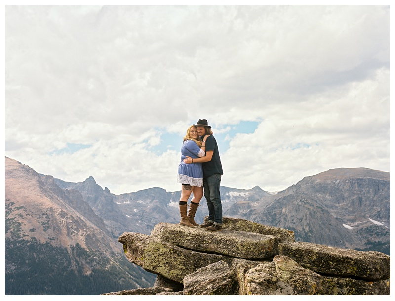 Stephanie and Daniel embrace on a rock with a view at Rocky Mountain National Park in Colorado. Engagement photography by Sonja Salzburg of Sonja K Photography.