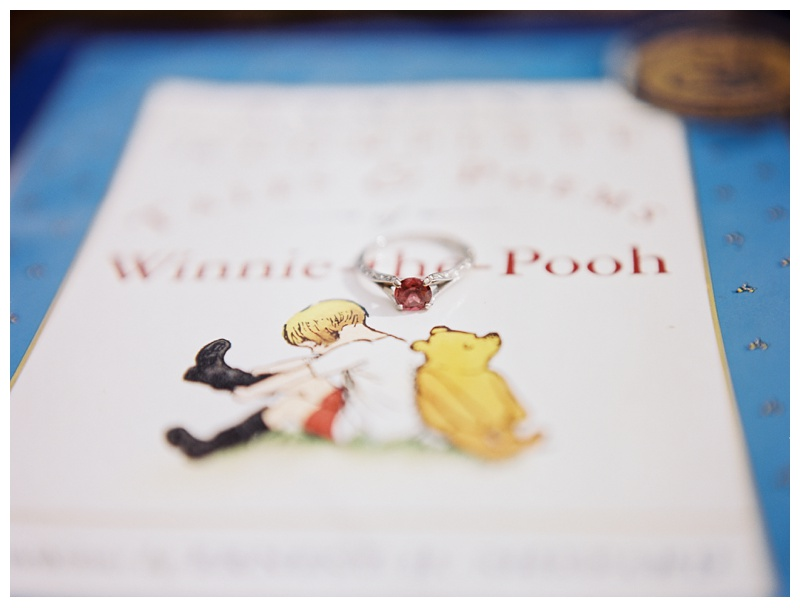 Stephanie's engagement ring on a copy of Winnie the Pooh. Engagement photography by Sonja Salzburg of Sonja K Photography.