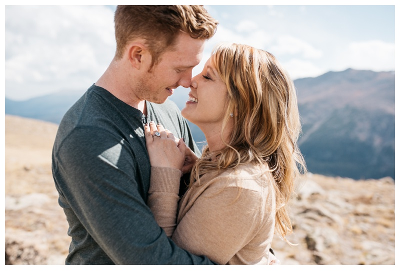 A newly engaged couple embrace on a warm Colorado day in Rocky Mountain National Park. Engagement photography by Sonja Salzburg of Sonja K Photography.
