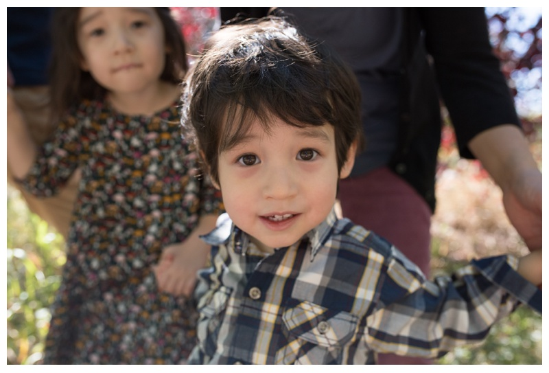 An adorable little boy with his family on a bright, sunny Fort Collins, Colorado day. Family portrait photography by Sonja Salzburg of Sonja K Photography.