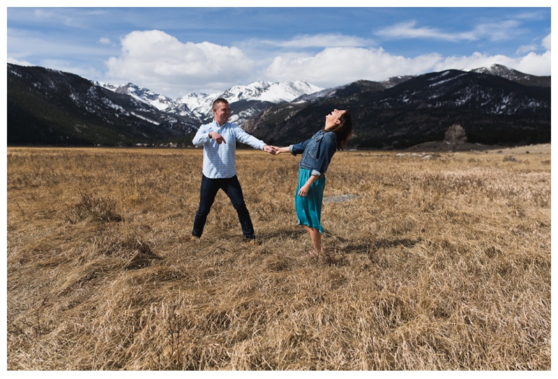 A happily engaged couple laughs at Sprague Lake in Rocky Mountain National Park in Colorado. Engagement photography by Sonja Salzburg of Sonja K Photography.