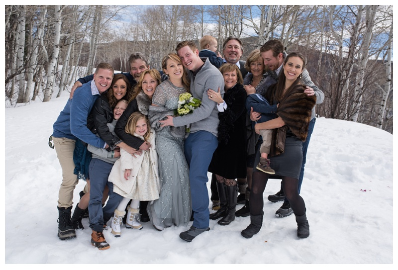 A happy family at a winter wedding ceremony at Rabbit Ears Pass outside of Steamboat Springs, Colorado. Wedding photography by Sonja Salzburg of Sonja K Photography.