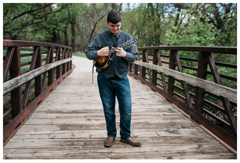 Eli Slocumb picks his mandolin on a bridge over the Poudre River at Lee Martinez Park in Fort Collins, Colorado. Portrait photography by Sonja Salzburg of Sonja K Photography.