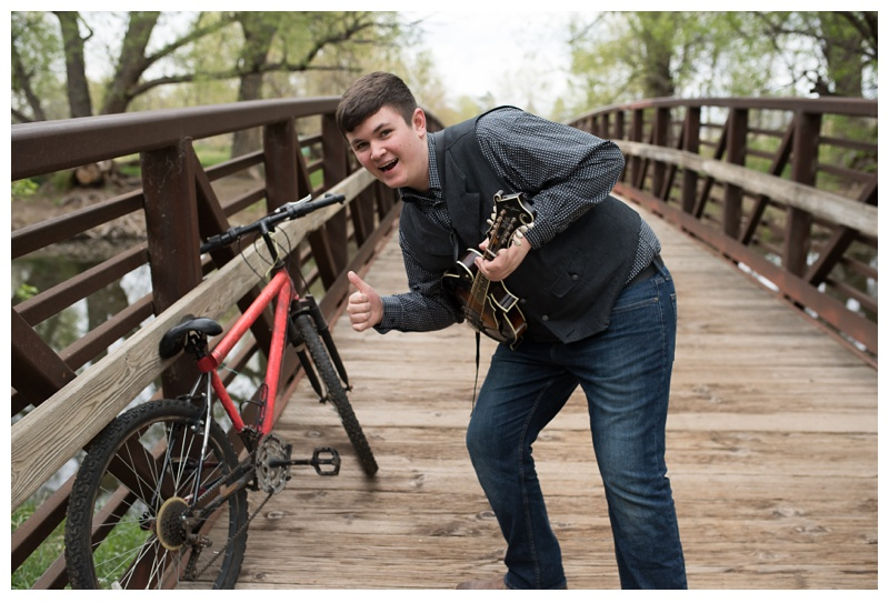 Eli Slocumb and a bike on the Poudre River bridge in Lee Martinez Park in Fort Collins, Colorado. Portrait photography by Sonja Salzburg of Sonja K Photography.