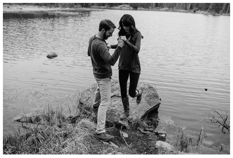 An engaged couple at a lake in Rocky Mountain National Park near Estes Park, Colorado. Wedding engagement photography by Sonja Salzburg of Sonja K Photography.