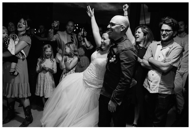 A bride and groom cheers their guests at Wolverine Farm Letterpress and Publick House in Fort Collins, Colorado. Wedding photography by Sonja Salzburg of Sonja K Photography.