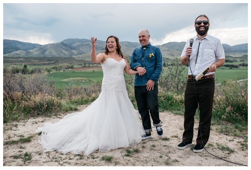 A bride and groom laughing during their wedding ceremony at Bingham Hill outside of Fort Collins, Colorado. Wedding photography by Sonja Salzburg of Sonja K Photography.
