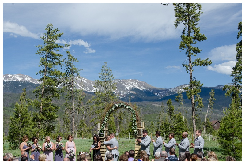 A bride a groom kiss as they are married at Wild Horse Inn in the Colorado Rockies near Winter Park and Fraser. Wedding photography by Max Salzburg of Sonja K Photography.