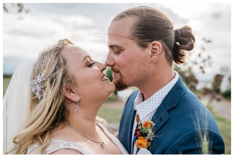 A bride and groom share an intimate moment on their wedding day at Meadows Event Center near Platteville, Colorado. Wedding photography by Sonja Salzburg of Sonja K Photography.