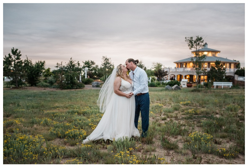 A bride and groom kiss at Meadows Event Center on their wedding day near Platteville, Colorado. Wedding photography by Sonja Salzburg of Sonja K Photography.
