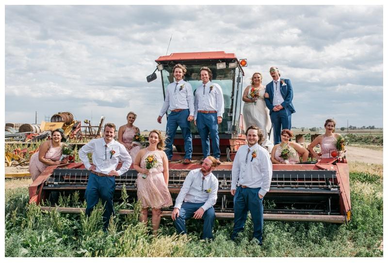 The wedding party on a tractor on a farm near Platteville, Colorado. Wedding photography by Sonja Salzburg of Sonja K Photography.
