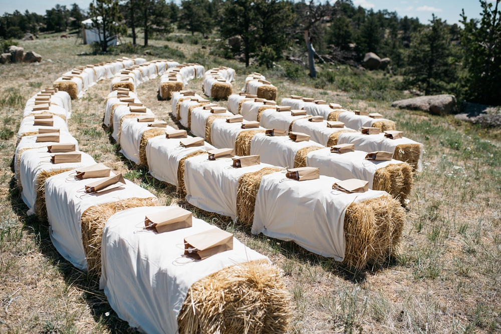 A hay bale ceremony site at a wedding outside of Cheyenne, Wyoming. Wedding photography by Sonja Salzburg of Sonja K Photography.