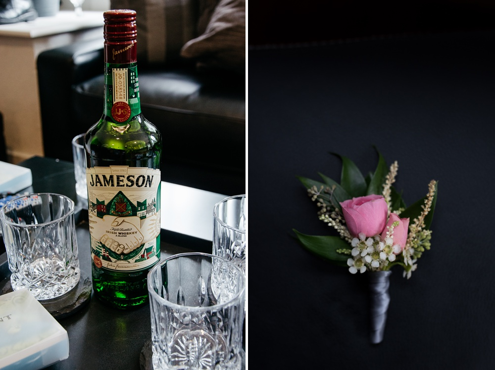 A special bottle of Jameson Irish Whisky and a boutonniere from an outdoor wedding at Wedgewood on Boulder Creek outside of Boulder, Colorado. Wedding detail photography by Sonja and Max Salzburg of Sonja K Photography.