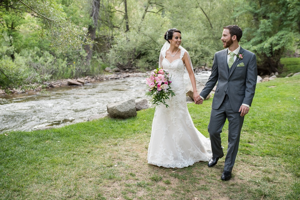 A couple walk by the creek on their wedding day at Wedgewood on Boulder Creek near Boulder, Colorado. Wedding photography by Sonja Salzburg of Sonja K Photography.