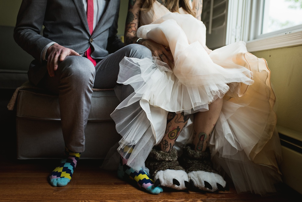 A bride and groom in their colorful socks and monster slippers. Wedding photography by Sonja Salzburg of Sonja K Photography.