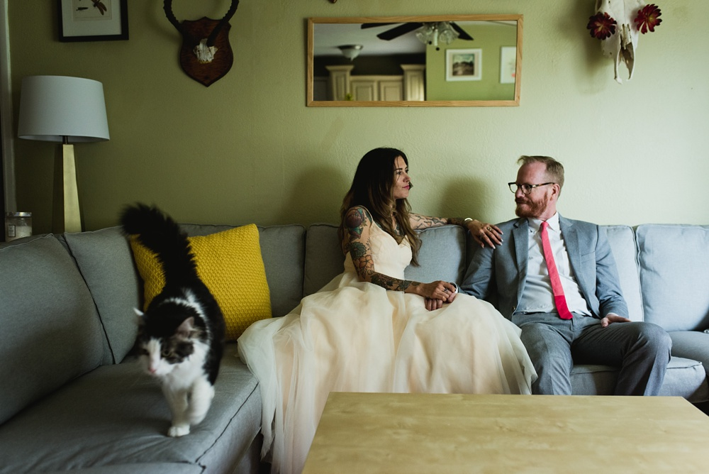 A couple relaxes in their home on their wedding day. Wedding photography by Sonja Salzburg of Sonja K Photography.