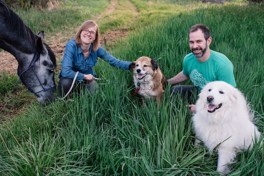 A young family with their dogs and horse at Poudre River Stables in Fort Collins, Colorado. Family portrait photography by Sonja Salzburg of Sonja K Photography.