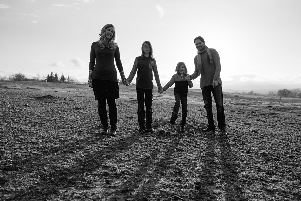 A black and white image of a happy family at Standley Lake in Westminster, Colorado. Family and engagement portrait photography by Sonja Salzburg of Sonja K Photography.