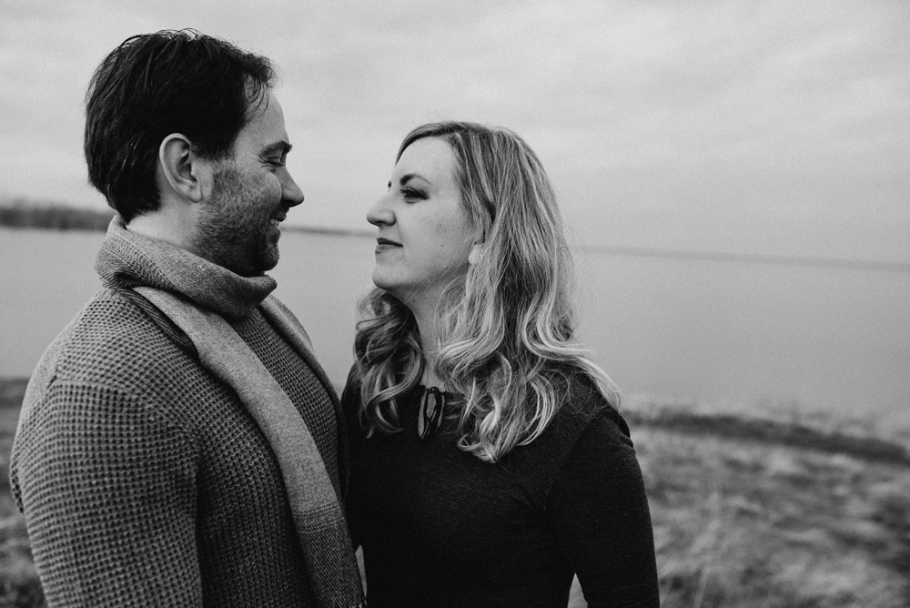 An engaged couple at Standley Lake in Westminster, Colorado. Engagement portrait photography by Sonja Salzburg of Sonja K Photography.