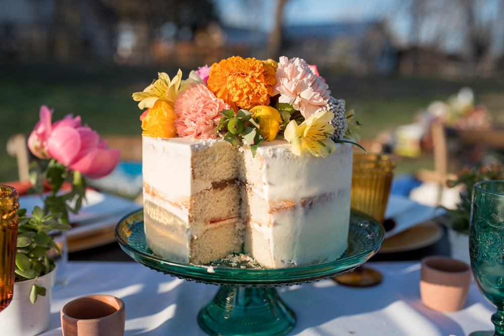 A cake by June Poppies on a table designed by Gumption and Grace at a styled shoot at Rist Canyon Inn outside of Laporte, Colorado. Wedding, styled shoot, and food and beverage photography by Sonja Salzburg of Sonja K Photography.