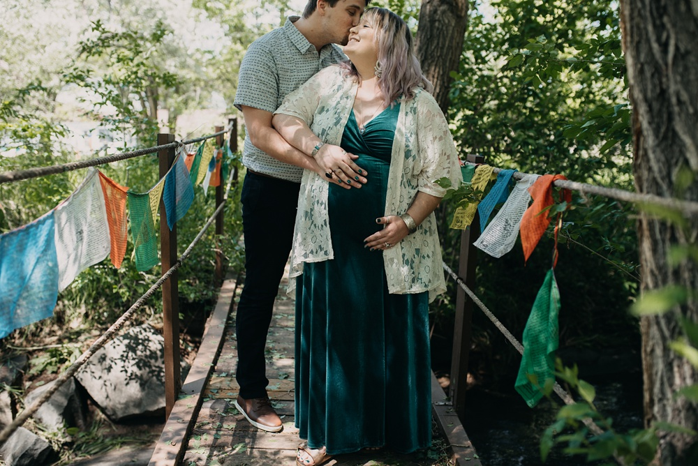 An expecting couple surrounded by prayer flags at Solarium International Inn and Hostel in Fort Collins, Colorado. Maternity portrait photography by Sonja Salzburg of Sonja K Photography.