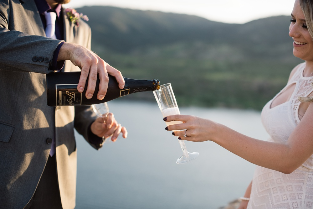 A bride a groom pour champagne on their wedding day at Horsetooth Reservoir outside of Fort Collins, Colorado. Wedding detail photography by Sonja Salzburg of Sonja K Photography.
