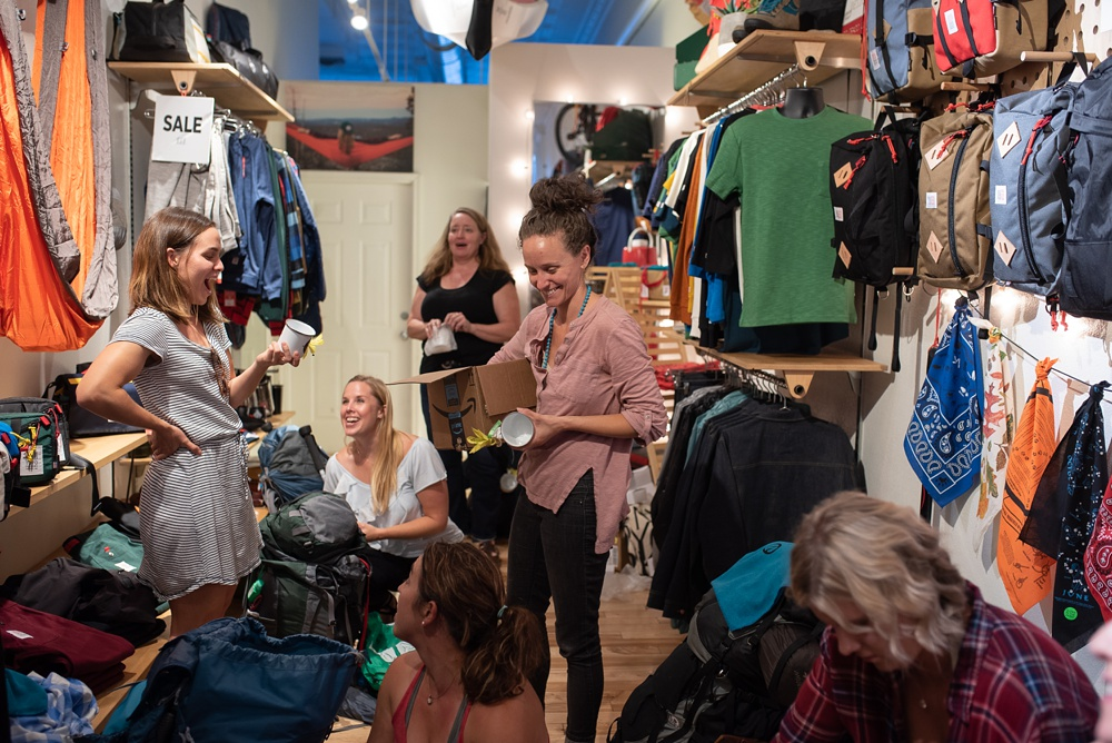 Copper cups are handed out by Emma of Wellbody Woman at the Summer TRIBE Program at Topo Designs in Old Town Fort Collins, Colorado. Corporate event photography by Sonja Salzburg of Sonja K Photography.