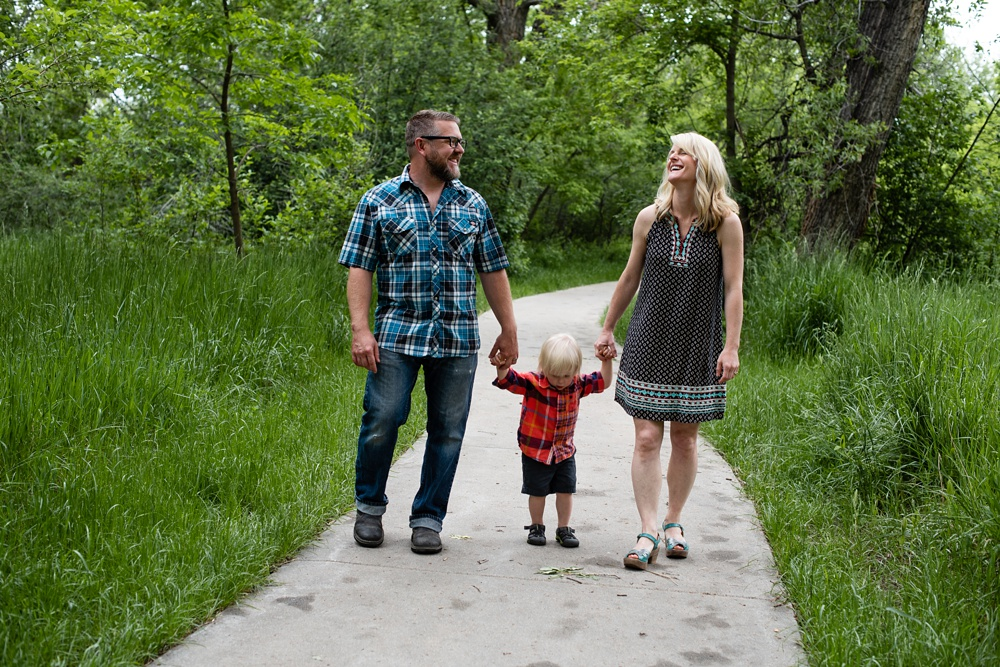 A young happy family walks on the trail near the Poudre River at Watson Lake outside of Fort Collins, Colorado.