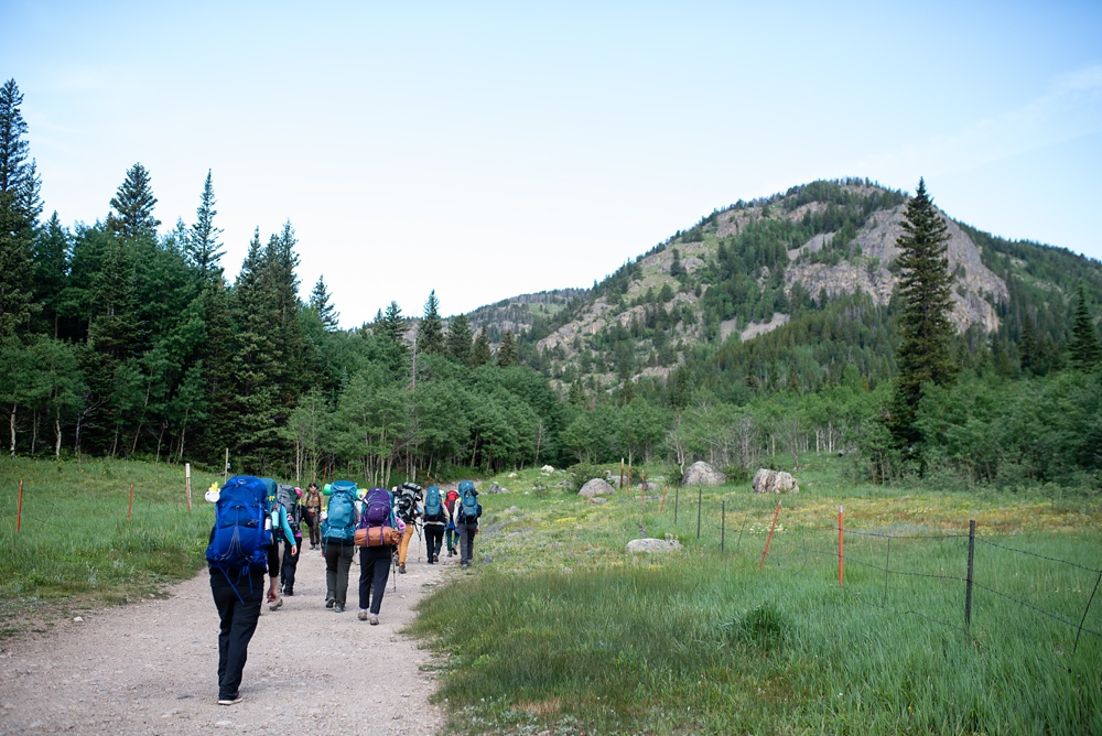 A group of women backpackers hike into the Indian Peaks Wilderness with the Wellbody Woman Summer TRIBE Program. Outdoor event photography by Sonja Salzburg of Sonja K Photography.