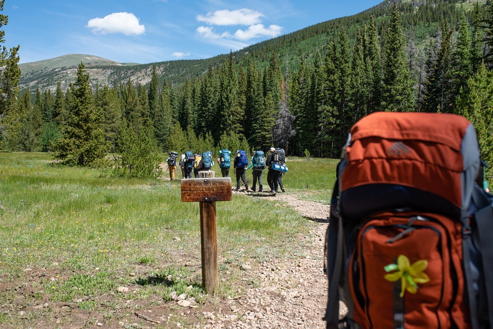 Hikers pass a sign on the way into the Indian Peaks Wilderness in Colorado on the Summer TRIBE Program by Wellbody Woman. Outdoor event photography by Sonja Salzburg of Sonja K Photography.
