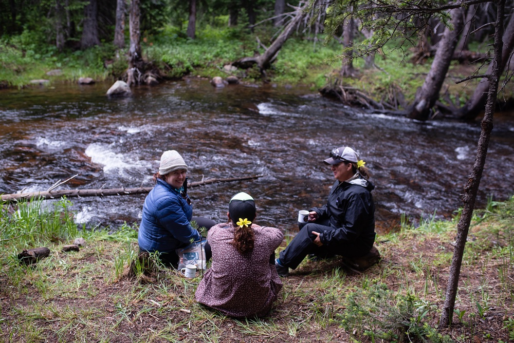 Participants sit by the creek and eat their breakfast and drink their coffee at the Wellbody Woman Summer TRIBE Program in the Indian Peaks Wilderness. Event photography by Sonja Salzburg of Sonja K Photography.