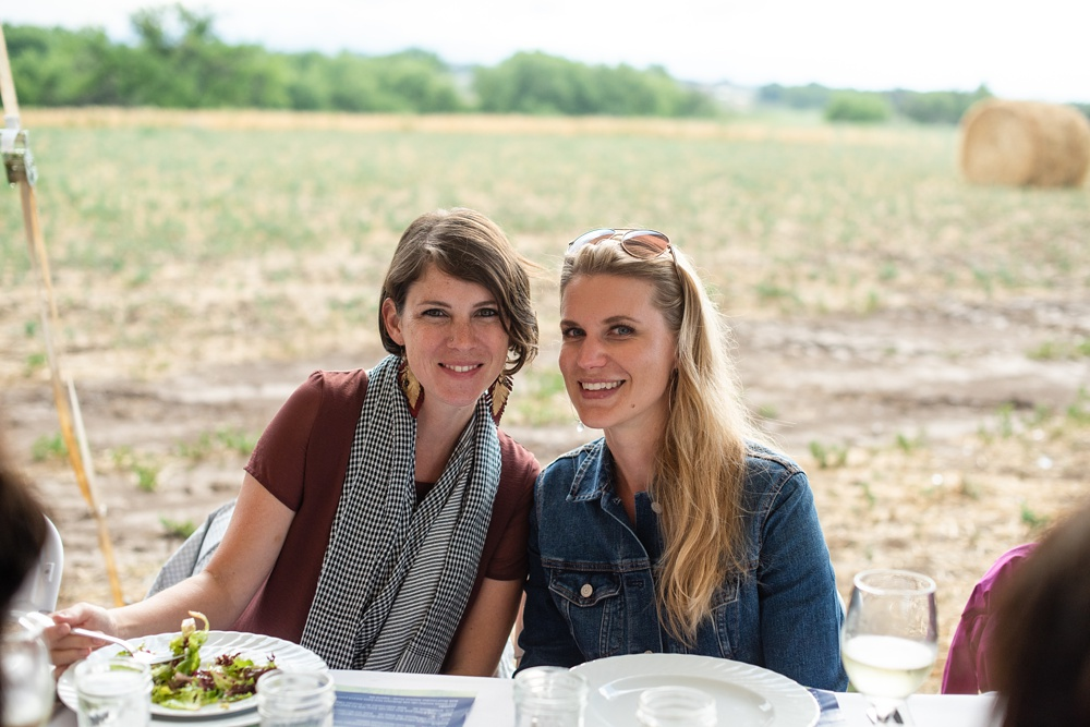 People enjoying the Fortified Collaborations Heart of Summer Farm Dinner at Colorado Stock and Grain Farm in Colorado. Event portrait and Food and Beverage photography by Sonja Salzburg of Sonja K Photography.