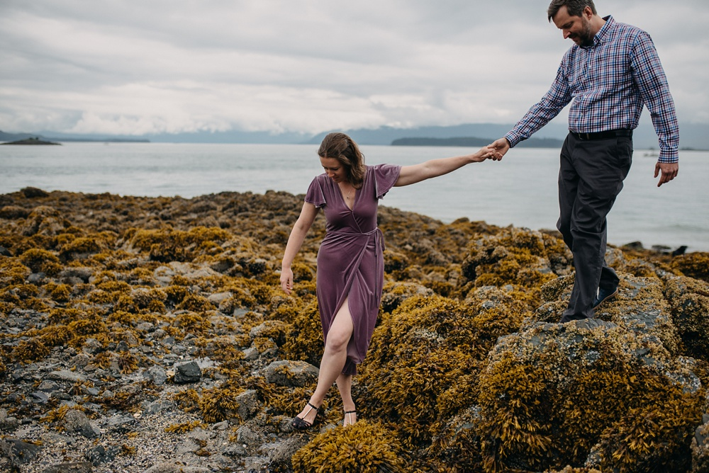 An engaged couple on the rocky beach at Pearl Harbor near the Jensen-Olson Arboretum outside of Juneau, Alaska. Engagement portrait photography by Sonja Salzburg of Sonja K Photography.