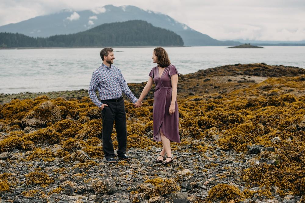 An engaged couple on a rocky beach near Juneau, Alaska. Engagement portrait photography by Sonja Salzburg of Sonja K Photography.