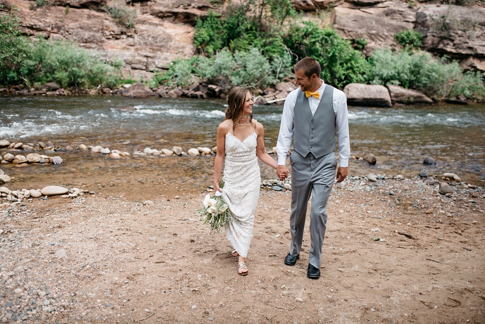 A married couple on the banks of the Cache la Poudre River at Watson Lake outside of Fort Collins, Colorado. Outdoor wedding photography by Sonja Salzburg of Sonja K Photography.
