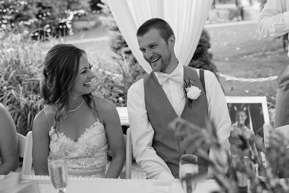 A bride and groom laugh at their reception on their wedding day at the Tapestry House in Laporte, Colorado. Wedding photography by Sonja Salzburg of Sonja K Photography.