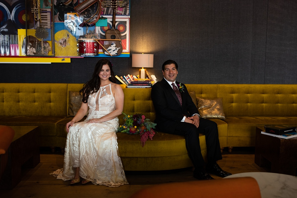 A bride and groom sit on a yellow couch on their wedding day at the Magic Rat inside the Elizabeth Hotel in Fort Collins, Colorado. Wedding portrait photography by Sonja Salzburg of Sonja K Photography.