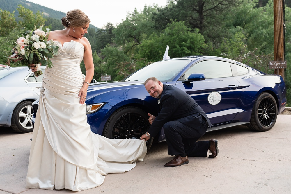A groom cleans his tires with his bride's dress at a wedding at Wedgewood Weddings on Boulder Creek outside of Boulder, Colorado. Wedding photography by Sonja Salzburg of Sonja K Photography.