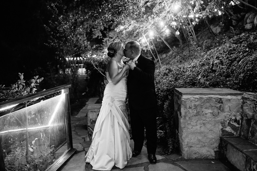 A bride and groom kiss on their wedding day at Wedgewood Weddings on Boulder Creek outside of Boulder, Colorado. Wedding photography by Sonja Salzburg of Sonja K Photography.