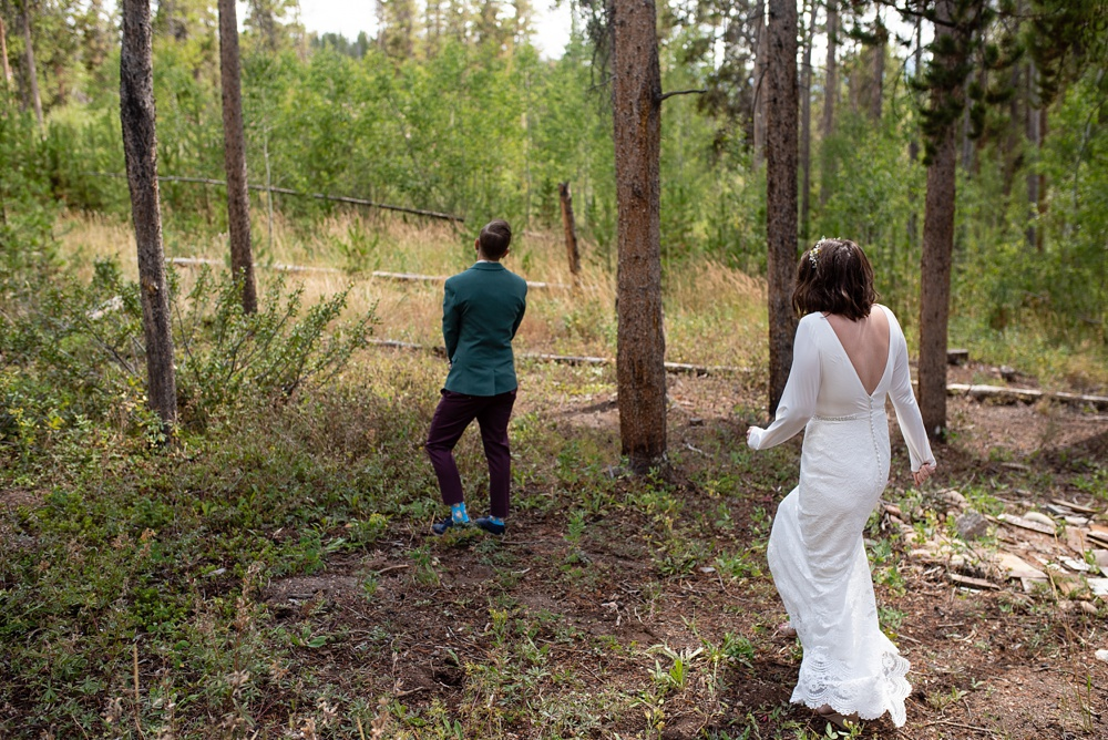 Two brides participate in a first look on their wedding day near Fraser, Colorado. Gay wedding photography by Sonja Salzburg of Sonja K Photography.