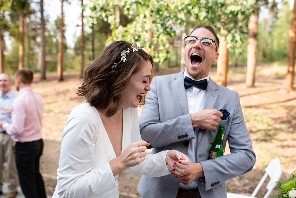 A bride and a guest share a laugh at her lesbian wedding in Fraser, Colorado. Gay wedding photography by Sonja Salzburg of Sonja K Photography.