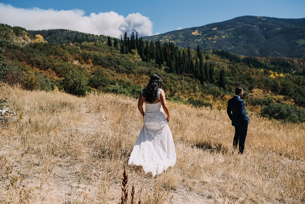 A bride walks to her groom in a first look at Bella Vista Estate in Steamboat Springs, Colorado, with the smoke from a summer fire in the background. Photography by Sonja Salzburg of Sonja K Photography