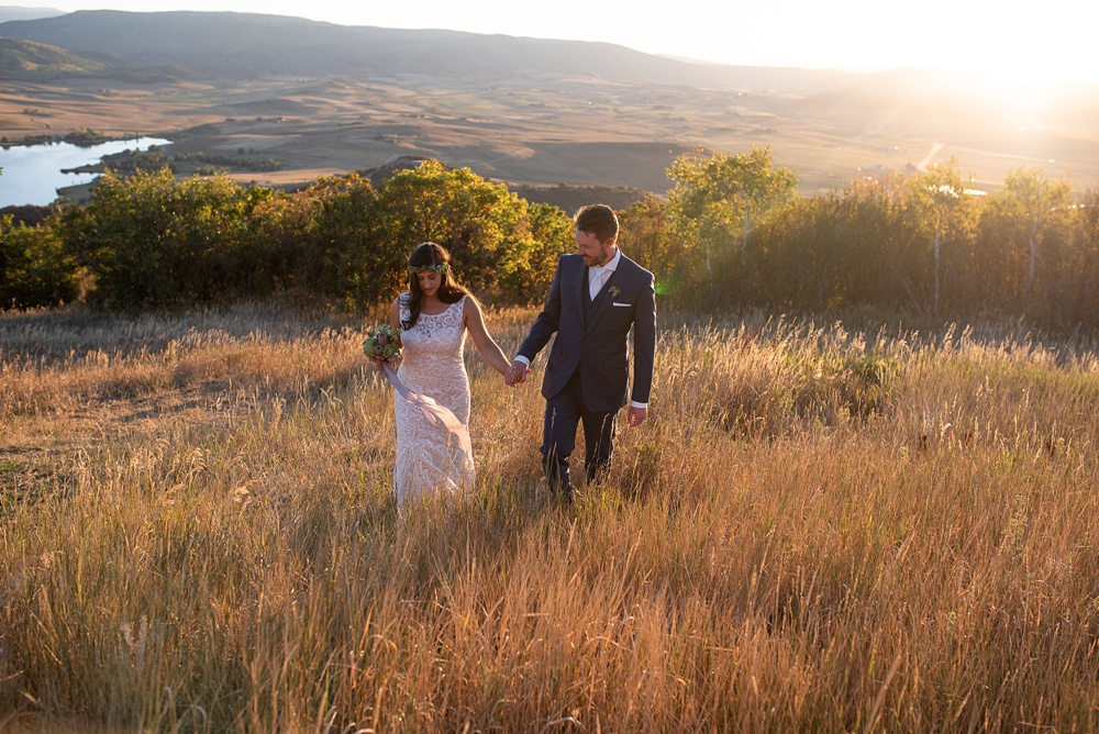 A bride and groom hold hands as they walk through a field of fall colors during the sunset on their wedding day in Steamboat Springs, Colorado at Bella Vista Estate. Photography by Sonja Salzburg of Sonja K Photography