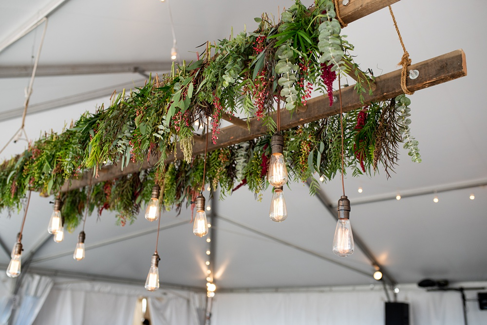 A bohemian fresh floral hanging lights display above the reception at Bella Vista Estate in Steamboat Springs, Colorado by Hop Rabbit Flowers. Photography by Sonja Salzburg of Sonja K Photography.
