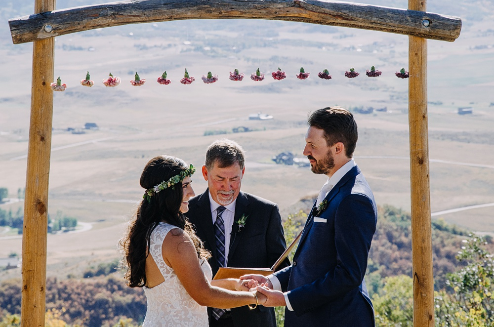 Outdoor ceremony with a bride and groom standing under their wedding arch at Bella Vista Estate in Steamboat Springs, Colorado with ombre flowers. Photography by Sonja Salzburg of Sonja K Photography