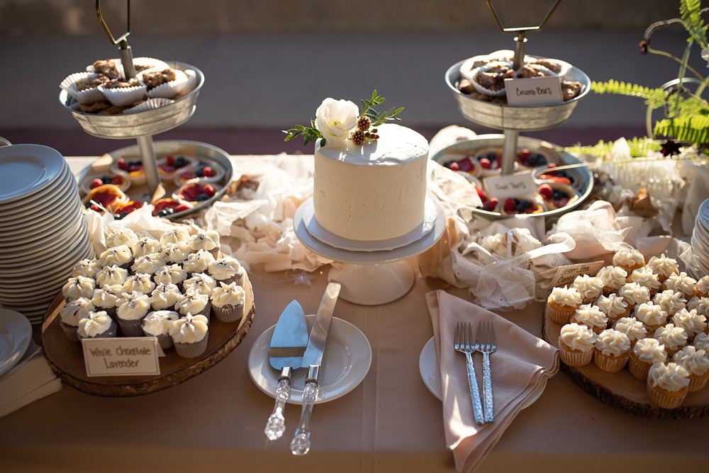 The sunsets behind the dessert table with a simple naked wedding cake and gluten free cupcakes for the wedding inspiration in Steamboat Springs, Colorado at the Bella Vista Estate. Photography by Sonja Salzburg of Sonja K Photography