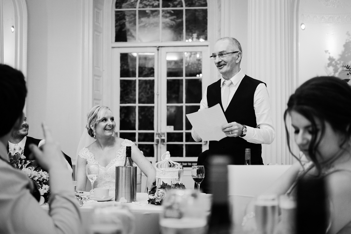Bride laughing at her dad's speech during the wedding, taken in black and white. Photographed at Colwick Hall, Nottingham